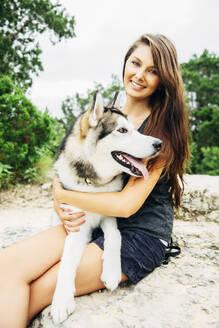 Caucasian woman petting dog outdoors - BLEF11190