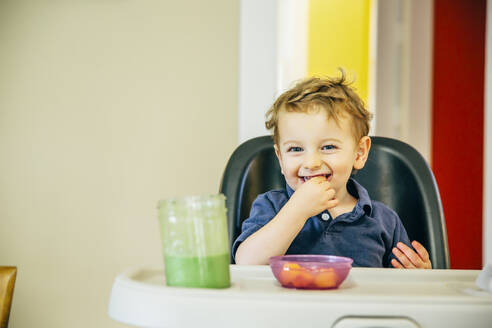 Caucasian boy eating in high chair - BLEF11196