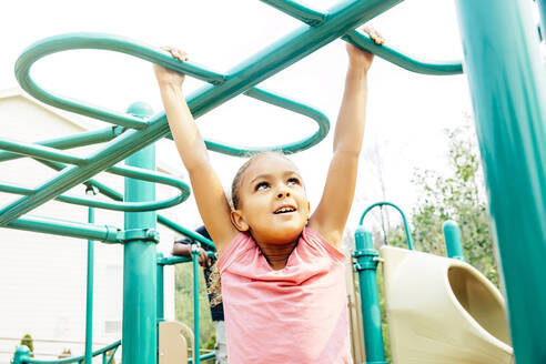 Mixed race girl playing on playground - BLEF11205