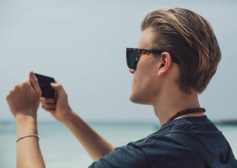 Caucasian man photographing seascape - BLEF11250