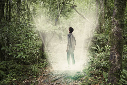 Mixed race boy standing in forest portal - BLEF11334