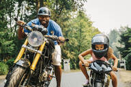Father and daughter sitting on motorcycles - BLEF11361