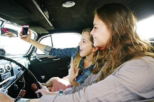 Friends taking selfie in vintage car - BLEF11463