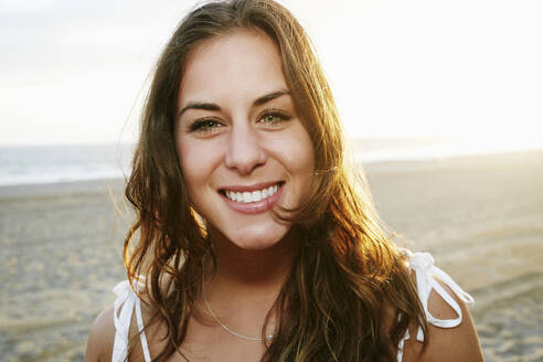 Mixed race woman smiling on beach - BLEF11478