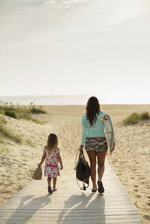 Mother and daughter walking on beach - BLEF11511