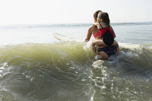 Mother and daughter surfing in waves - BLEF11526