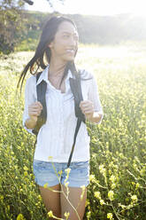 Mixed race woman carrying backpack in field - BLEF11676