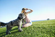Caucasian woman sitting in field with dog - BLEF11703
