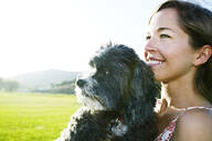 Caucasian woman holding dog outdoors - BLEF11706