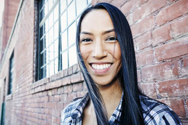Mixed race woman smiling at brick wall - BLEF11709