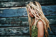 Black woman with dreadlocks at wooden wall - BLEF11712