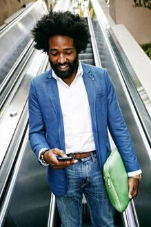 Mixed race businessman using cell phone on escalator - BLEF11754