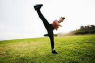 Black woman kick boxing in field - BLEF11763