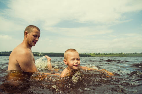 Caucasian father and son swimming in lake - BLEF11847