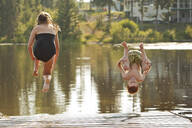 Caucasian children jumping into lake - BLEF11853