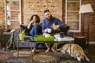 Couple enjoying breakfast on sofa in living room - BLEF11904