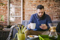 Caucasian man drinking coffee on sofa in living room - BLEF11907
