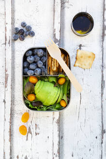 Lunchbox with salad, avocado and yellow tomatoes, crackers, blueberries and salad dressing - LVF08194