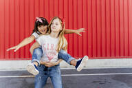 Girl carrying her sister on back, standing in front of a red wall - ERRF01619