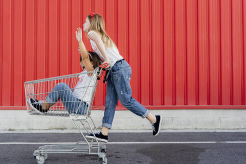 Sisters with shopping cart in front of red wall - ERRF01634