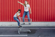 Sisters with shopping cart in front of red wall - ERRF01637