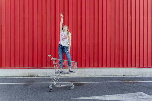 Girl in a shopping cart pointing finger up in front of red wall - ERRF01646