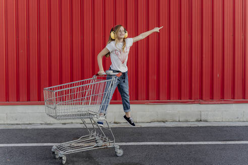 Girl with a shopping cart and ear defender in front of red wall - ERRF01655