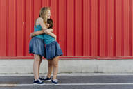 Sisters hugging in front of a red wall - ERRF01664
