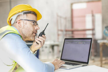 Architect using laptop and walkie talkie at construction site - ZEF16154