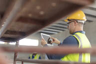 Architect using laptop at construction site - ZEF16160