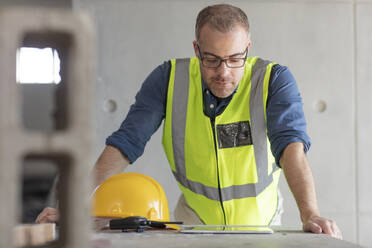 Architect using laptop at construction site - ZEF16163