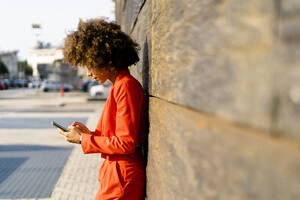 Young woman wearing fashionable red pantsuit leaning against wall using cell phone - GIOF06864