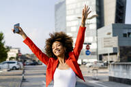 Portrait of happy young woman with smartphone wearing fashionable red suit jacket - GIOF06888