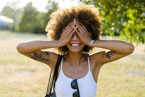 Smiling tattooed young woman in summer covering eyes with her hands - GIOF06903