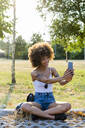 Portrait of tattooed young woman  taking selfie with smartphone in summer - GIOF06906