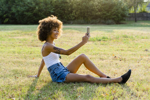 Tattooed young woman sitting on a meadow taking selfie with smartphone - GIOF06912
