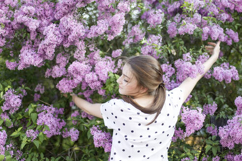 Young woman embracing a lilac shrub - JESF00243
