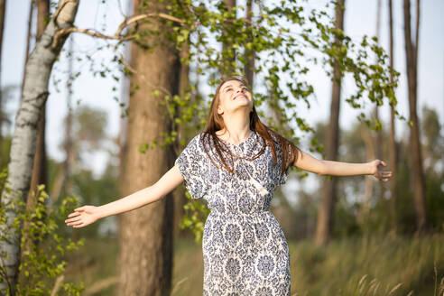 Deutschland, Jerichower Land, Gommern: Junge Frau im Kleid dreht sich vor Freude im Wald - JESF00249