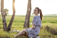 Smiling young woman sitting on a tree trunk and enjoying sunset - JESF00252