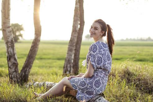 Deutschland, Jerichower Land, Gommern: Junge Frau sitzt auf einem Baumstamm im Birkenwald und schaut in den Sonnenuntergang - JESF00252
