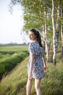 Deutschland, Jerichower Land, Gommern: Junge Frau im Kleid läuft in einem Birkendwald entlang und sucht Entspannung - JESF00255