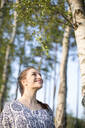 Smiling young woman enjoying nature in a forest - JESF00258