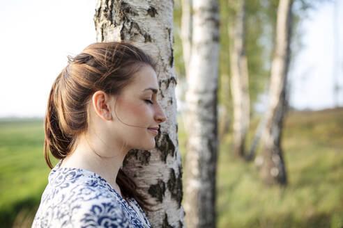 Deutschland, Jerichower Land, Gommern: Junge Frau im Kleid entspannt im Wald - JESF00261