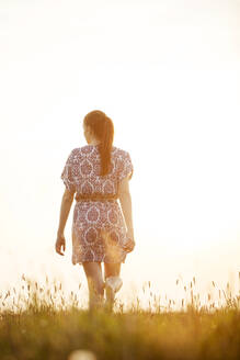 Young woman walking across a meadow in sunset - JESF00264