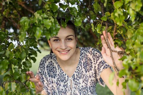 Deutschland, Jerichower Land, Gommern: Junge Frau im Sommerkleid schaut aus einem großen Baum hervor und genießt die Natur im Sonnenuntergang - JESF00267