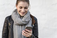 Smiling young woman using her smartphone - JESF00270