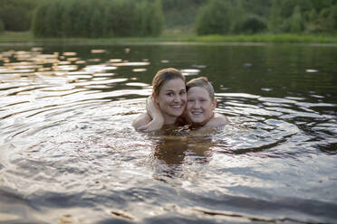 Portrait of happy mother and son bathing in a lake by sunset - VPIF01381
