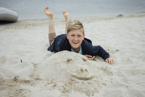Portrait of happy blond boy with freckles wearing hooded jacket in front of Zeya River, Russia - VPIF01387