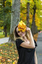 Portrait of smiling woman with bunch of autumn leaves on avenue - JUNF01676