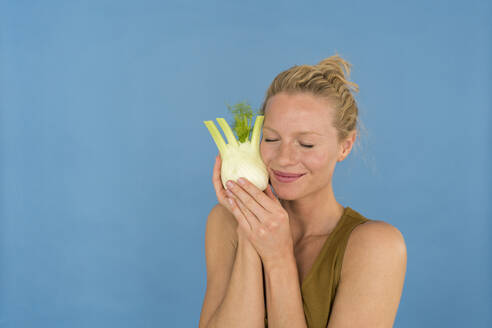 Smiling blond woman with closed eyes and fennel, blue background - JOSF03565